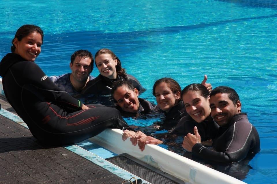 קבוצת אנשים עם חליפות צלילה יושבים בבריכה ומחייכים למצלמה