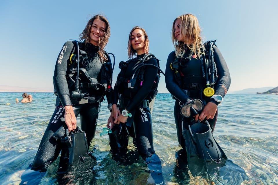 שלוש צוללות עומדות במים עד גובה ברכיים, מחזיקו סנפירים ומסכלות למצלמה